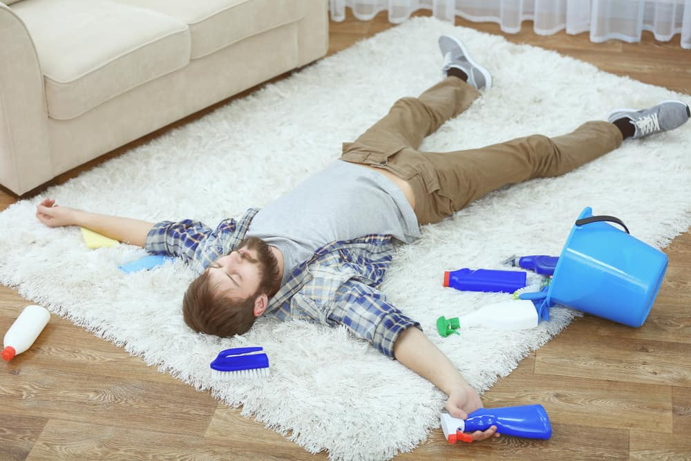 man lying on top of carpet after diy cleaning